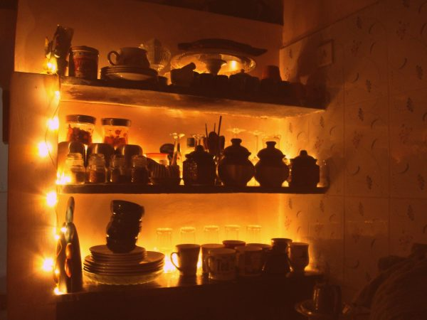 The kitchen shelf lined with fairy lights behind the canisters to provide a little more light to a dark kitchen.