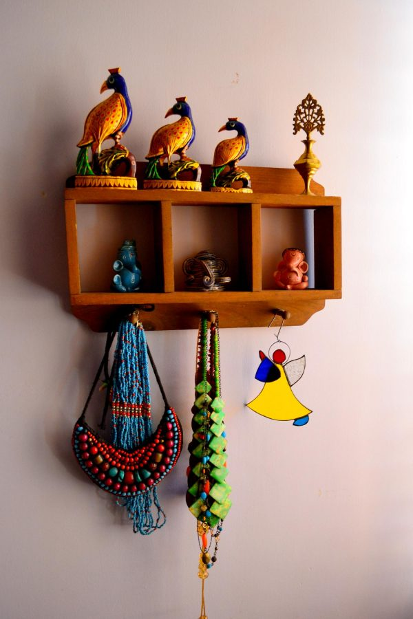 A small wooden wall shelf that has three ceramic ganeshas, and also used as jewelry display.