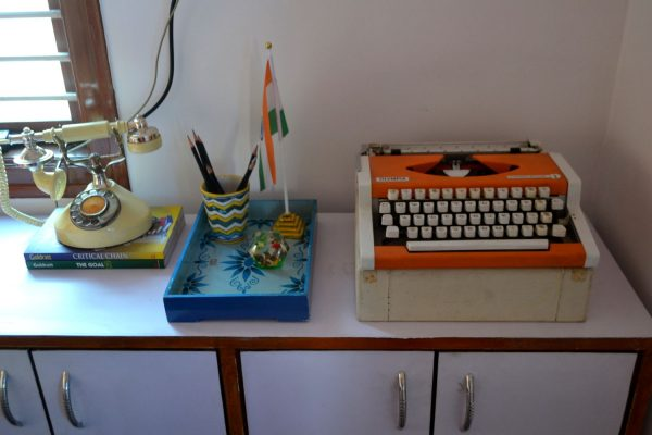 A vintage typewriter alongside a old dial ring phone.