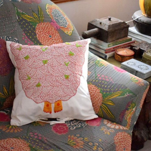 A gorgeous embroidered pillow cover on a kantha embroidery couch.