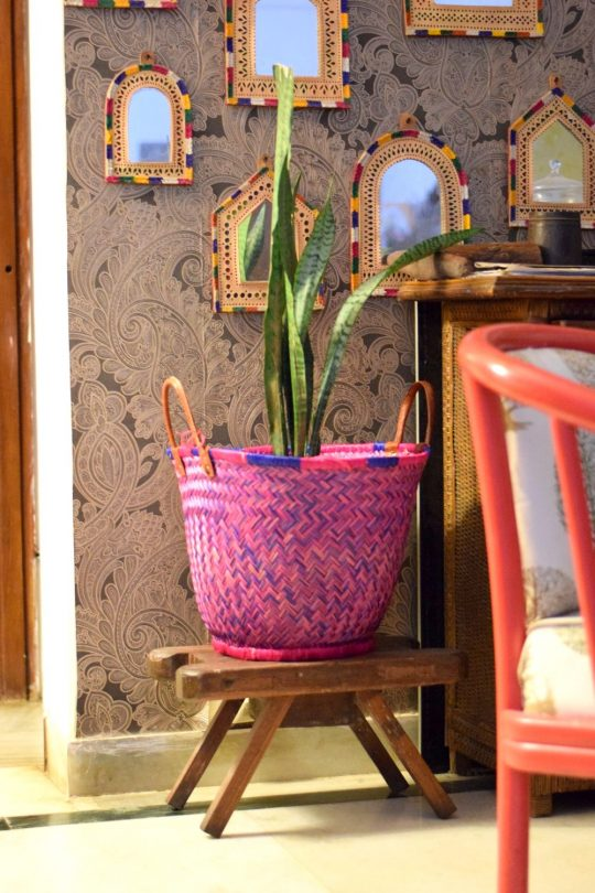 A Pink and blue bohemian planter against a mirror wall